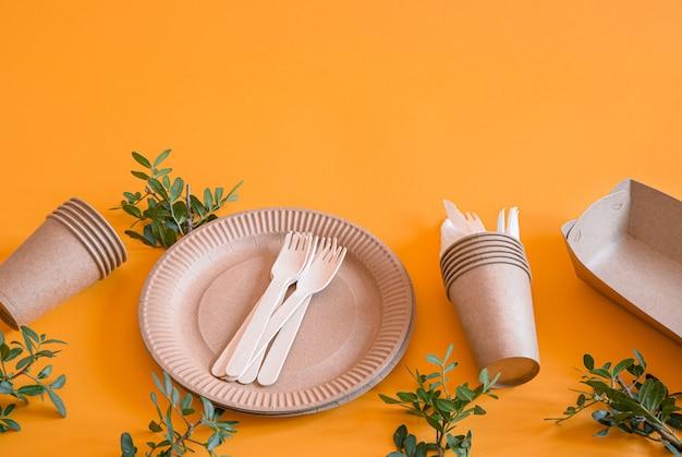 Platos desechables ecológicos hechos de papel en una pared naranja