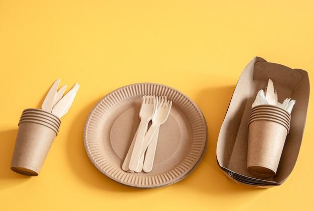 Platos desechables ecológicos hechos de papel sobre una superficie naranja