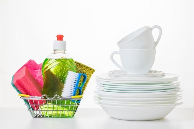 Platos y detergentes de cerámica blanca sobre una superficie clara