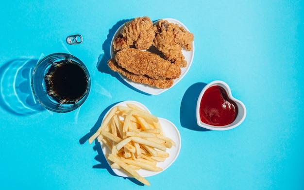 Platos en forma de corazón con bocadillos sobre un fondo azul nuggets alas tiras y papas fritas con ketchup sol sombras duras