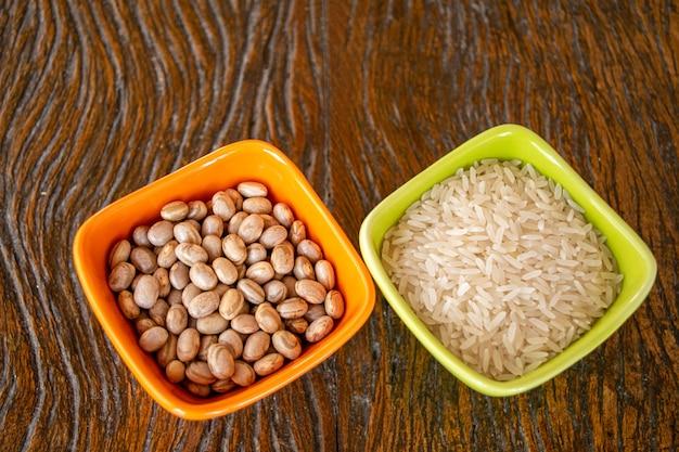 Platos con granos de arroz blanco y frijoles en mesa de madera