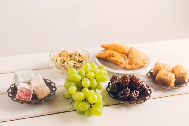 Platos orientales y uvas sobre mesa.