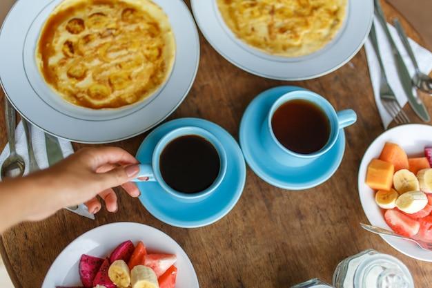Platos con panqueques de plátano, frutas tropicales y dos tazas de café en la mesa de madera,