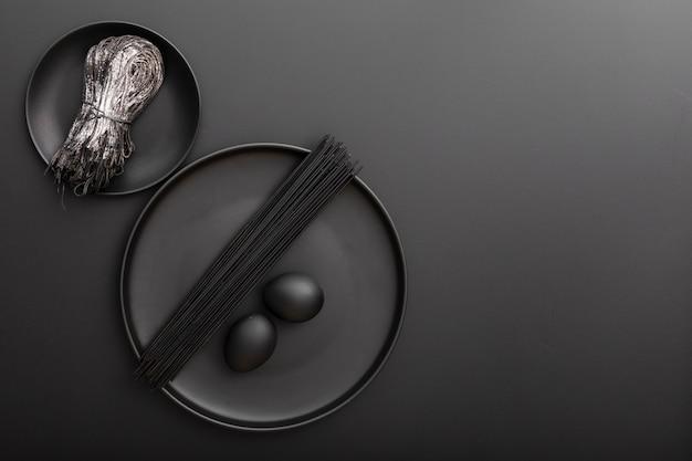 Platos con pasta y huevos sobre una mesa oscura