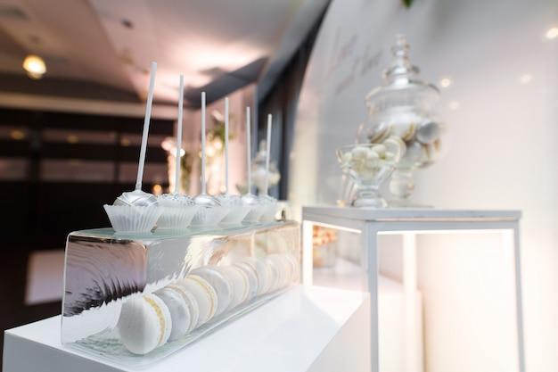 Platos con pastelitos y malvaviscos. barra de caramelo en la fiesta festiva de cumpleaños o boda aislada. dulces en la mesa festiva de cerca