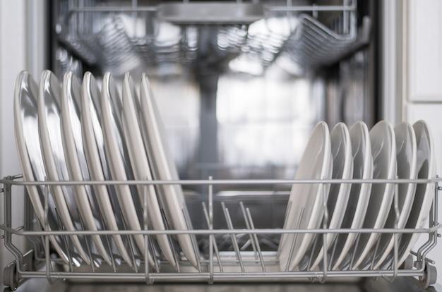 Los platos planos blancos grandes y pequeños se cargan en el lavavajillas.