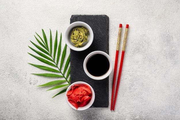 Platos planos de wasabi de jengibre y tazones de salsa de soja en pizarra