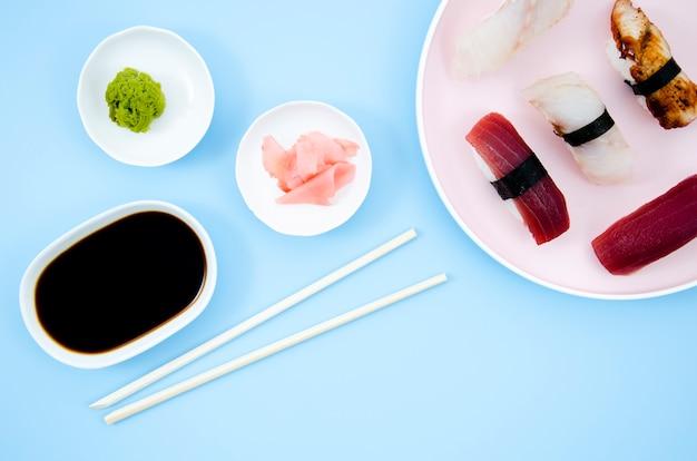 Platos con sushi y salsa de soja sobre un fondo azul.