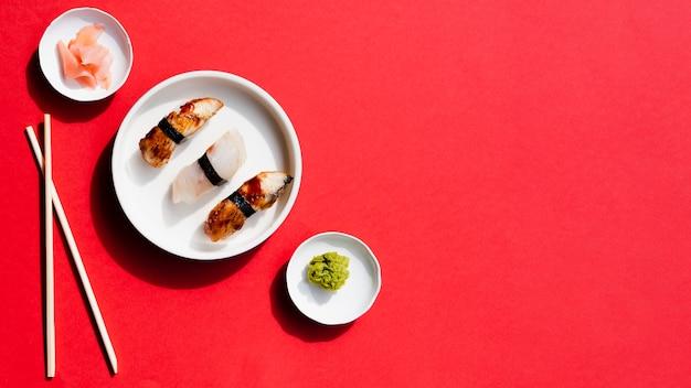 Platos con sushi y wasabi sobre un fondo rojo.