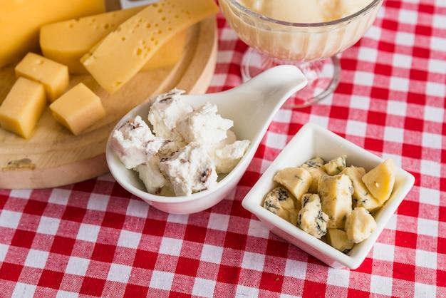 Platos y tabla de cortar con queso fresco en mesa.