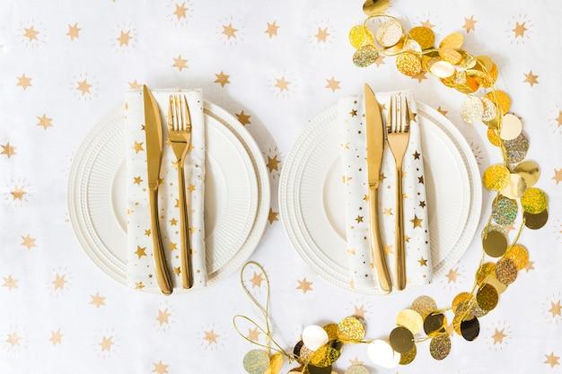 Platos con tenedor y cuchillo en mesa de luz.