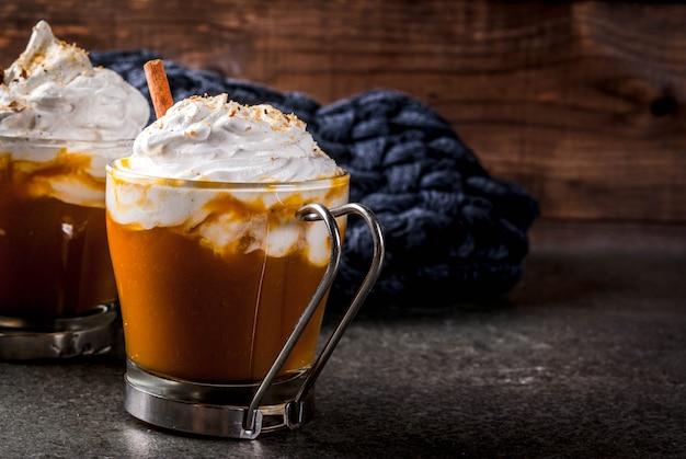 Platos tradicionales de otoño. halloween, acción de gracias. latte de calabaza aromática caliente y picante con canela sobre mesa de piedra negra, con una manta. copyspace