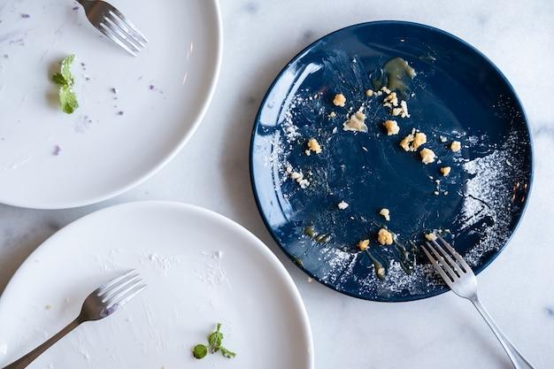 Platos vacíos de la torta con la bifurcación en la tabla