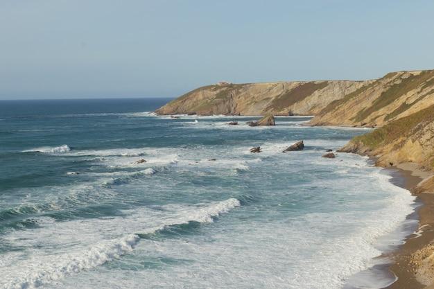 Playa y un acantilado de fondo. cabo vidio en cudillero, asturias, norte de españa.