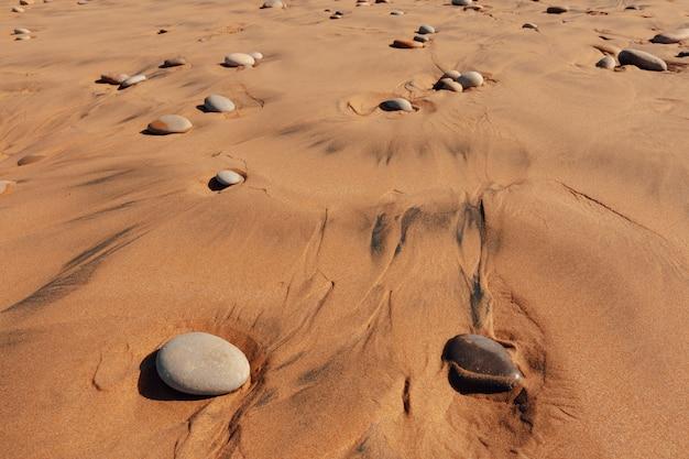 Playa de arena con guijarros, zona de surf. fondo natural, tema ecológico de viaje.