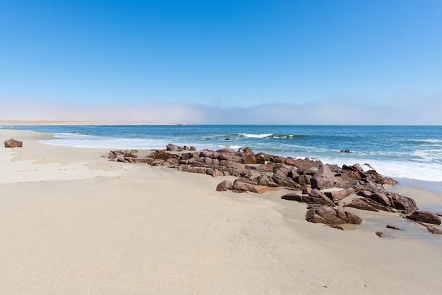 Playa de arena y línea costera en el océano atlántico en cape cross, namibia, famosa por la cercana colonia de focas. claro cielo azul.