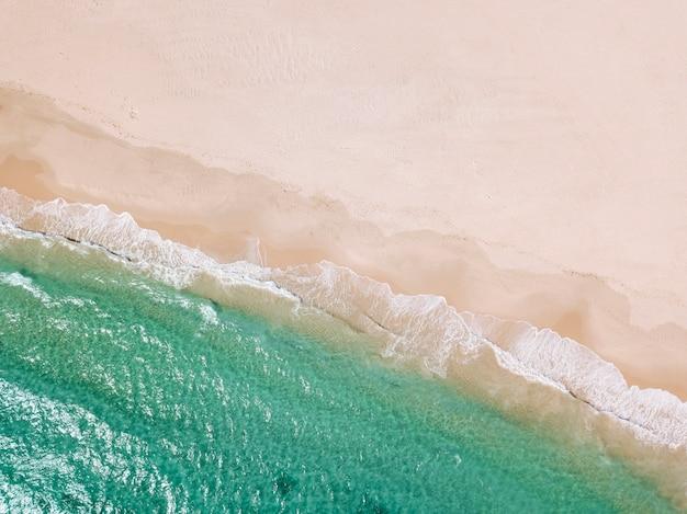 Playa de arena y línea de mar desde arriba.