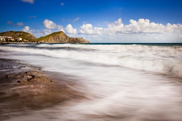 Playa de arena con montañas y cielo nublado