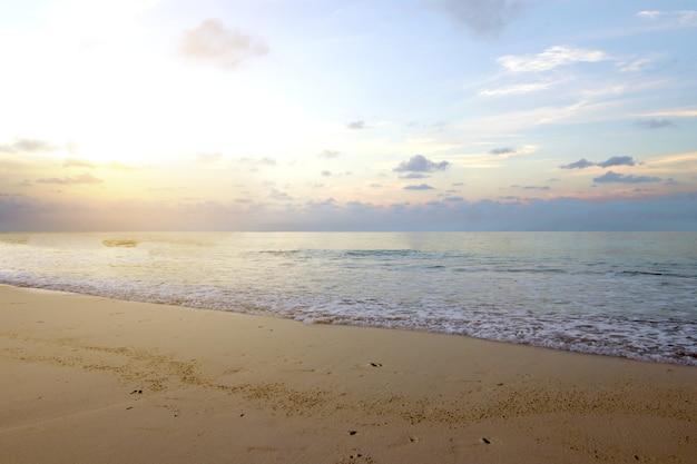 Playa de arena con el océano azul y el cielo al atardecer