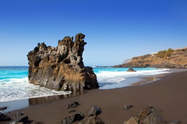 Playa el bollullo arena marrón negra y agua aqua.