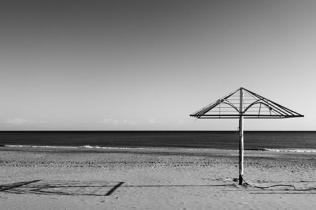 Playa desolada con sombrilla desnuda junto al mar. fotografía en blanco y negro, paisaje - marino