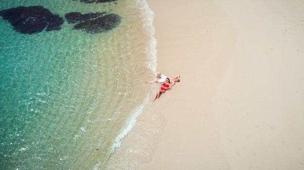 Playa drone vista isla tropical de phuket, playa blanca con olas, pareja tumbada en la playa. foto aérea.