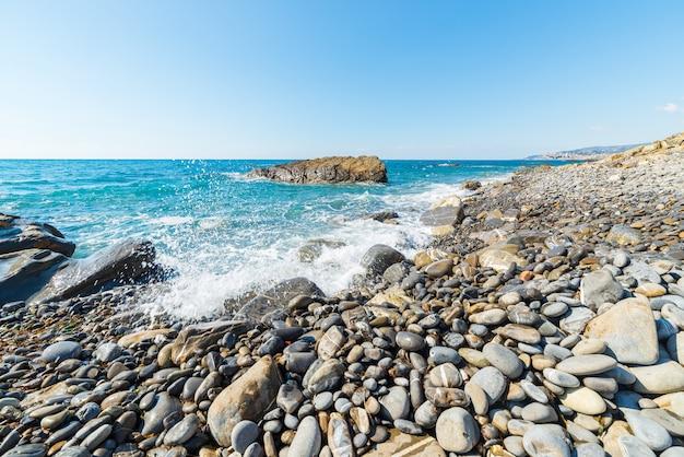 Playa de guijarros con salpicaduras de agua.