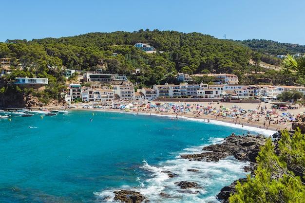 Playa llena de gente en la costa brava (cataluña, españa). destino de vacaciones de verano en europa