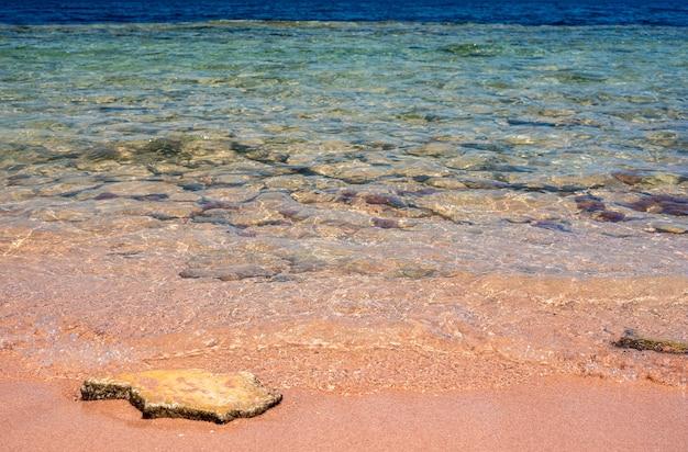 Playa y mar tropical closeup suave ola del mar en la playa de arena cielo azul en el mar playa de coral y agua azul a la luz del día temporada calurosa de verano en el mar tropical