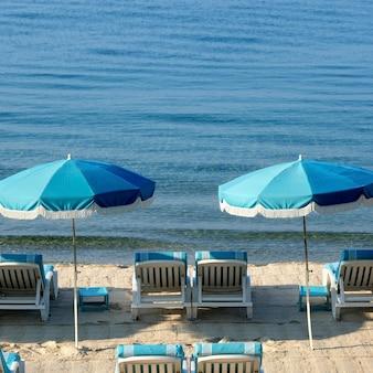 Playa mediterránea con sombrillas y sillas.