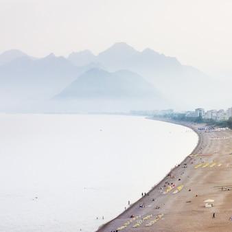 Playa y montañas en un día brumoso