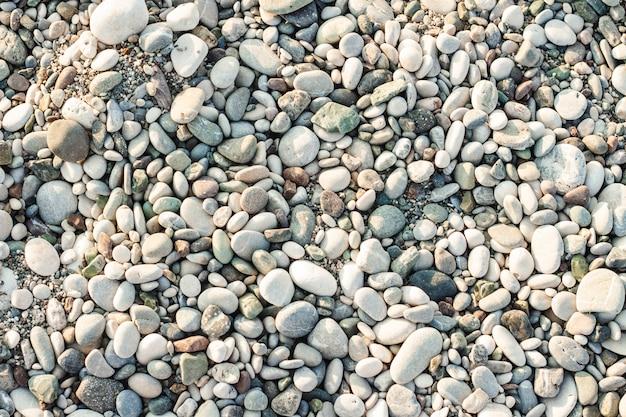 Playa de piedras de piedra. la textura de pequeñas piedras y arena. se puede usar como fondo de textura