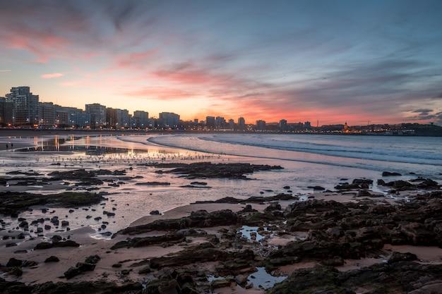 Playa durante una puesta de sol en gijón, españa
