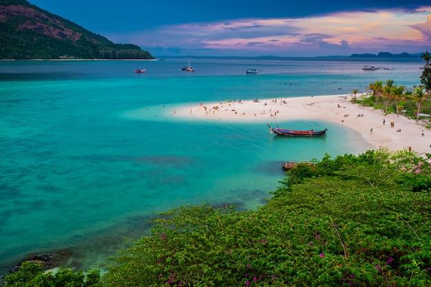 Playa que se extiende hacia el mar mirando hacia fuera para ver la isla y el cielo azul hay muchos botes flotando en el mar verde esmeralda del mar de andamán.