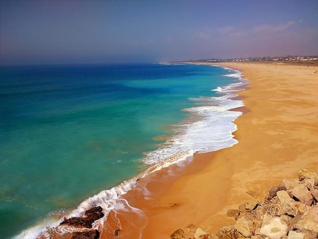 Playa rodeada por el mar bajo la luz del sol en cádiz, españa.
