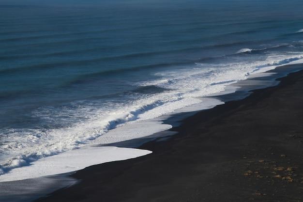 Playa rodeada por el mar bajo la luz del sol en islandia