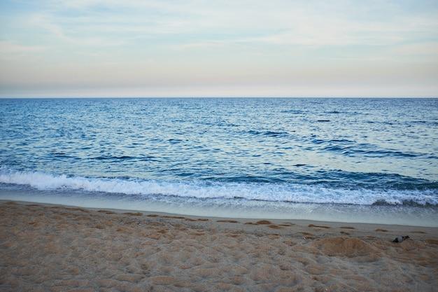 Playa salvaje para nadar sin gente después del atardecer sin sol.