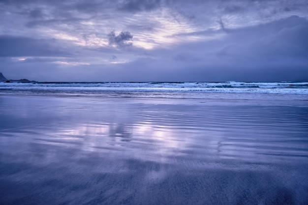 Playa de skagsanden en puesta de sol, islas lofoten, noruega