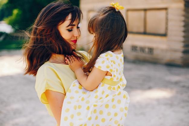 En una playa soleada de arena amarilla, mamá camina vestida de amarillo y su pequeña niña bonita