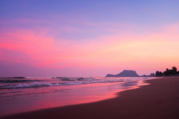 Playa soleada, tiro de gran angular de olas que chapotean suavemente en la playa de arena fina