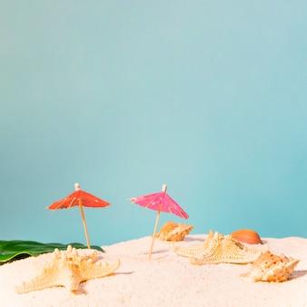 Playa con sombrillas rojas y estrellas de mar.
