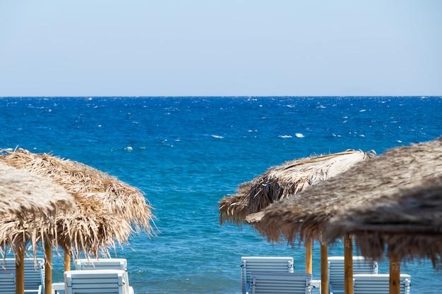 Playa con sombrillas y tumbonas junto al mar en santorini