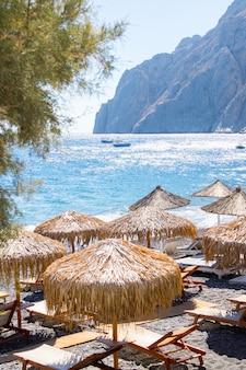 Playa con sombrillas y tumbonas en santorini