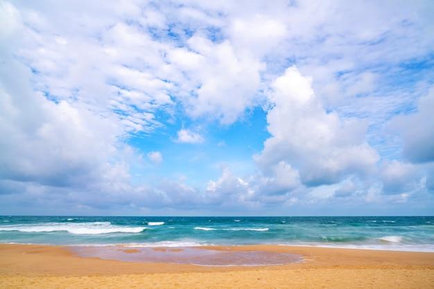 Playa tropical de arena con cielo azul y olas