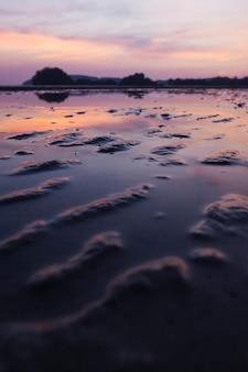Playa tropical de arena con cielo dramático durante la marea baja.
