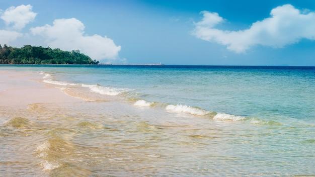 Playa tropical con olas suaves y verano de arena blanca con sol en vacaciones relajantes y naturaleza