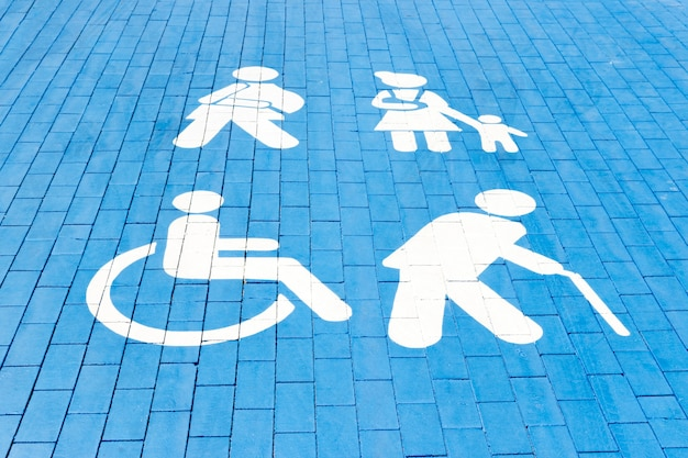 Plaza de aparcamiento para minusválidos, mamá con niño, anciano y hombre con yeso. cuadrado azul sobre asfalto.