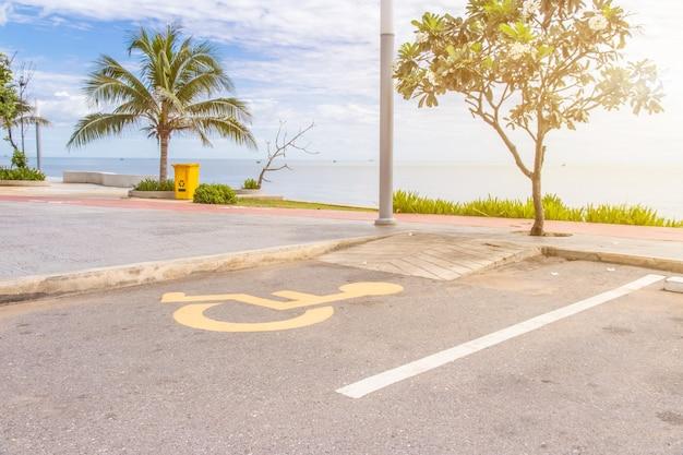 Plaza de aparcamiento para minusválidos con símbolo de discapacidad en el asfalto reservado para minusválidos