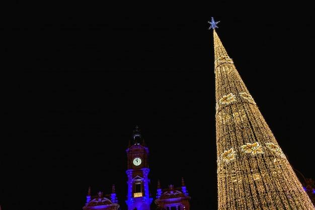 La plaza modernisme en valencia, españa, al anochecer, iluminada por un brillante árbol de navidad y edificio del ayuntamiento de la ciudad, al fondo.