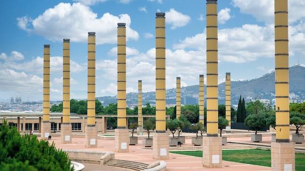 Plaza con vegetación y columnas, vista de barcelona al fondo, españa